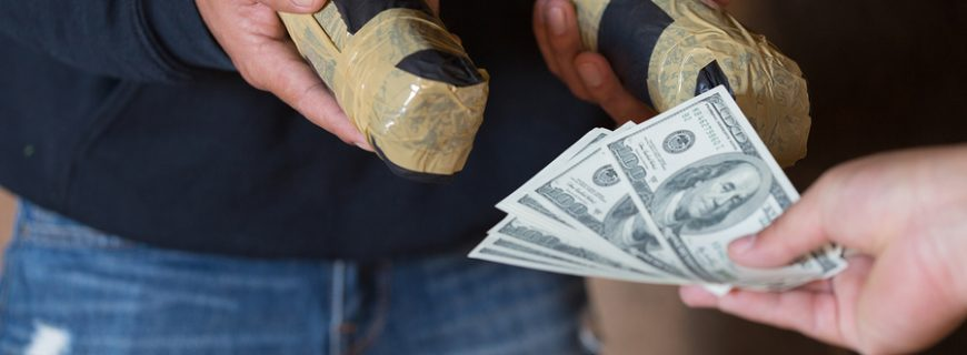 Hand of addict man with money buying dose of cocaine or heroine, close up of addict buying dose from drug dealer, drug trafficking, crime, addiction and sale concept,